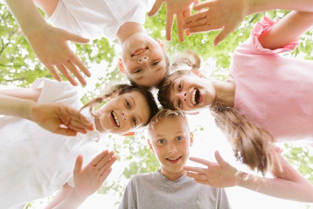 Kinder der ansicht von unten, welche die kamera betrachten