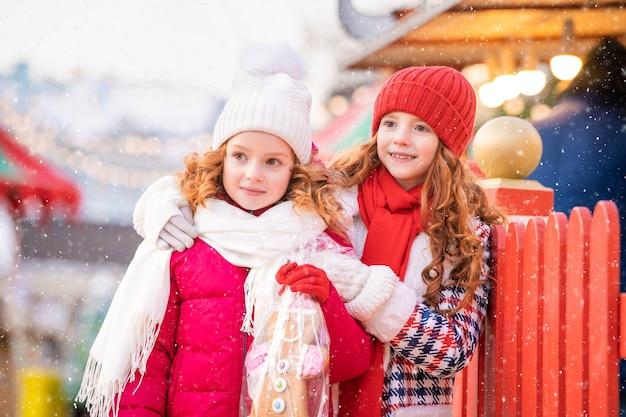 Kinder der rothaarigen schwestern gehen mit einem großen lebkuchen in der hand über einen festlich geschmückten weihnachtsmarkt in der stadt.