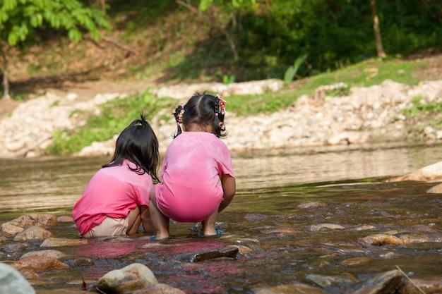 Kinder des kindes zwei, die spaß haben, im wasserfall zusammen in der sommerzeit zu spielen