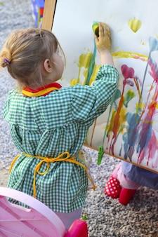 Kinder des kleinen mädchens des künstlers, die abstraktes bild malen