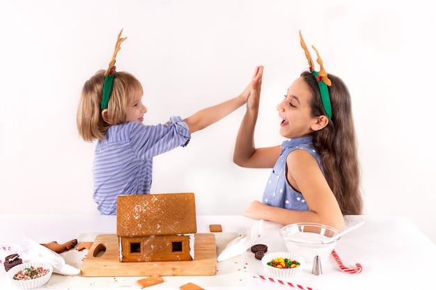 Kinder des weihnachtskonzeptes zwei machen das lebkuchenhaus, das auf weißem hintergrund lokalisiert wird.