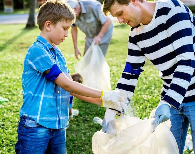 Kinder, die abfall im park aufheben