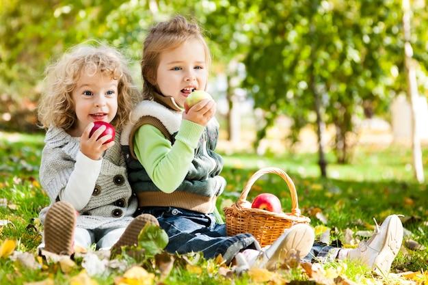 Kinder, die äpfel im herbstpark essen familienpicknick