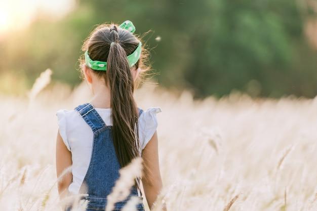 Kinder, die allein am feld während des schönen sonnenuntergangs stehen