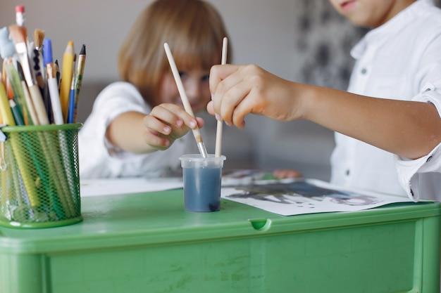 Kinder, die am grünen tisch und am zeichnen stationieren