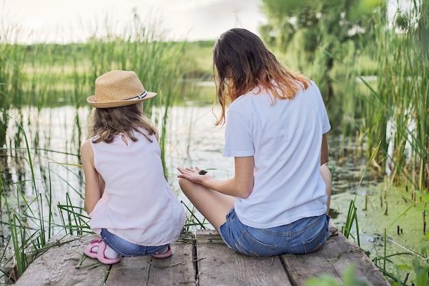Kinder, die am sonnigen sommertag in der nähe des wassers ruhen, zwei mädchen, die see betrachten, der auf brücke sitzt, sich entspannt, mit wasserschnecken spielend, rückansicht