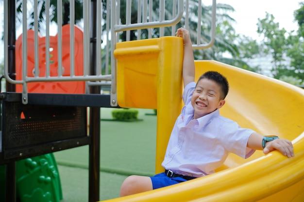 Kinder, die am spielplatz, glücklicher junge spielen