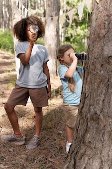 Kinder, die an einer schatzsuche im wald teilnehmen