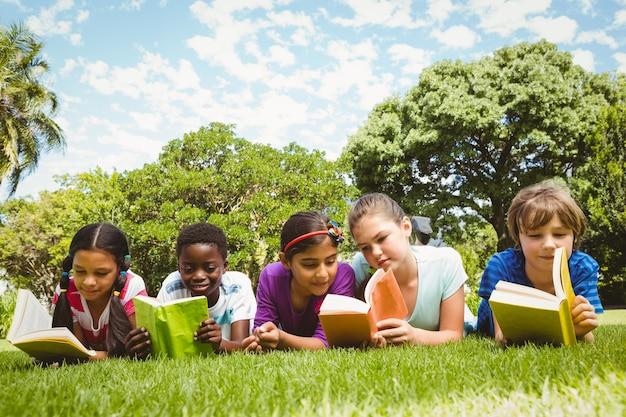 Kinder, die auf gras liegen und bücher lesen