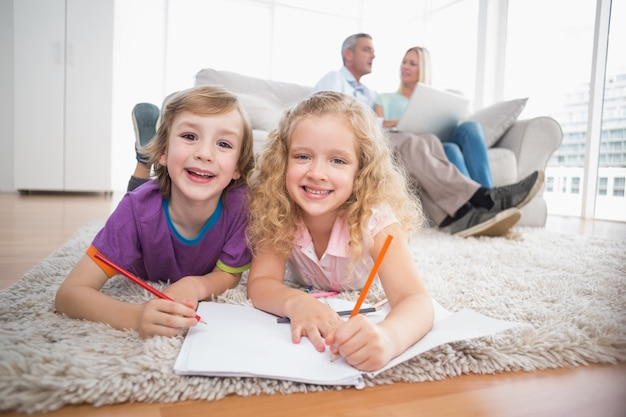 Kinder, die auf papiere während eltern sitzen auf sofa zeichnen