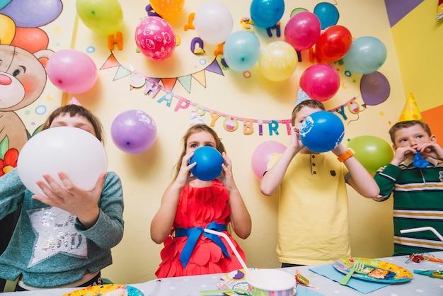 Kinder, die ballone auf geburtstagsfeier explodieren