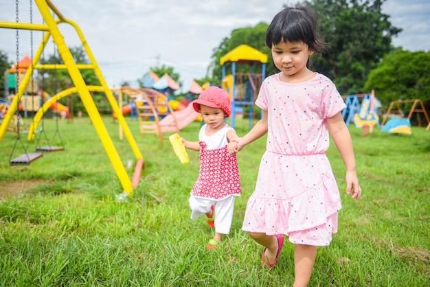 Kinder, die das kleine mädchen des spaßes hält hand zusammen mit der liebe spielt die äußeren asiatischen kinder glücklich im gartenpark mit spielplatz haben