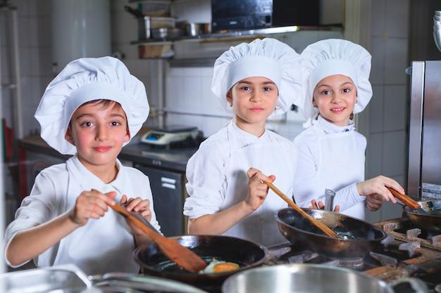Kinder, die das mittagessen in einer restaurantküche kochen.