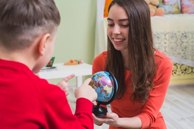 Kinder, die dem lehrer länder zeigen