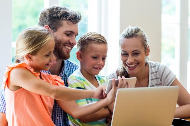 Kinder, die den eltern bei tisch telefon sitzen mit laptop zeigen
