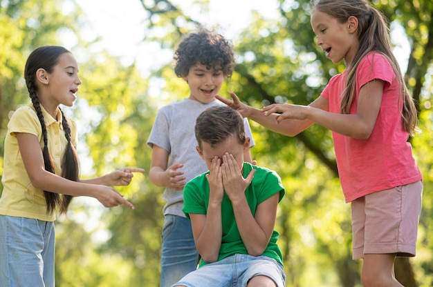 Kinder, die den jungen beleidigen, der das gesicht mit den händen bedeckt.
