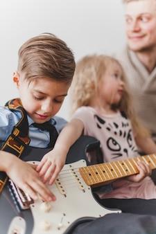 Kinder, die die gitarre ihres vaters berühren