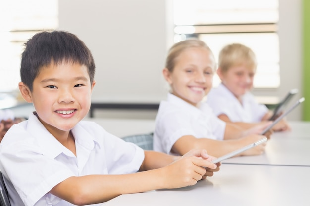 Kinder, die digitales tablet im klassenzimmer verwenden