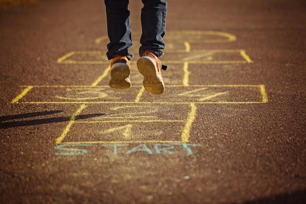 Kinder, die draußen hopse auf spielplatz spielen. hopscotch beliebtes straßenspiel