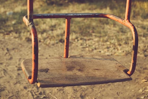 Kinder, die draußen rostiges metall des schwingens mit hölzernem sitz hängen