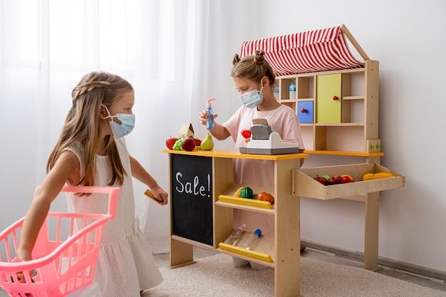 Kinder, die drinnen zusammen spielen, während sie gesichtsmasken tragen