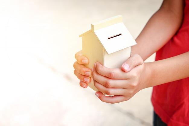 Kinder, die ein holzhaus halten, haben geldschlitze, um geld zu sparen, das sie in zukunft ausgeben können