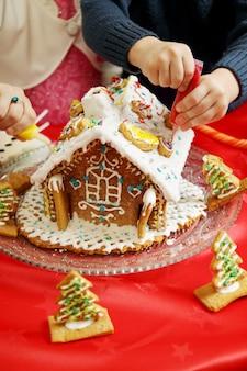 Kinder, die ein lebkuchenhaus verzieren