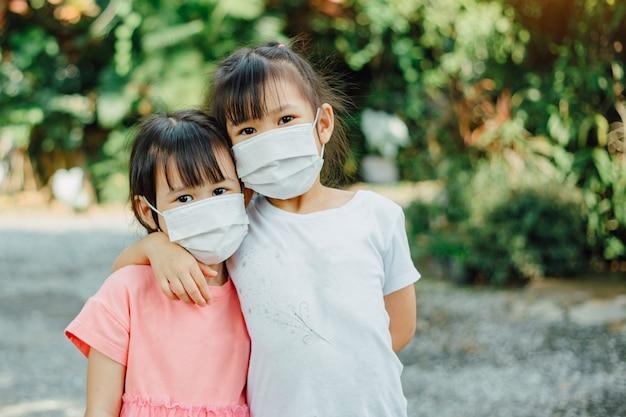 Kinder, die eine gesichtsmaske tragen, um sich vor viren zu schützen und die ausbreitung des ausbruchs des coronavirus covid 19 zu reduzieren