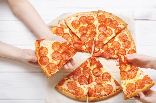 Kinder, die eine scheibe pizza halten.