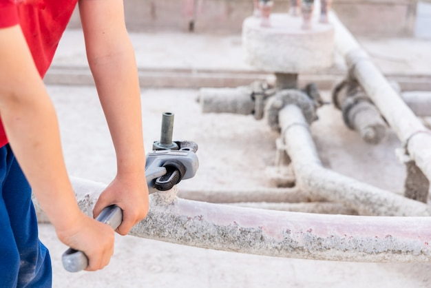 Kinder, die einen geraden hochleistungsrohr-sanitärschlüssel verwenden, um ein rohr zu reparieren.