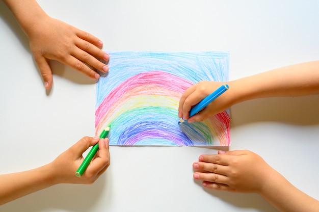 Kinder, die einen regenbogen auf weißem hintergrund zeichnen