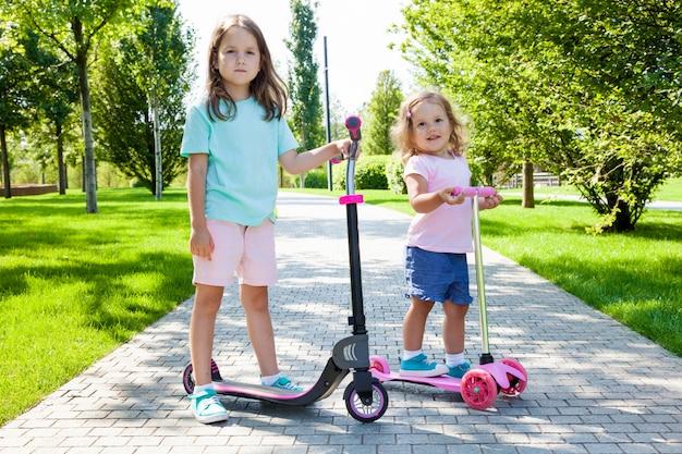 Kinder, die einen roller im park am sonnigen sommertag reiten. spaßaktivität für kind