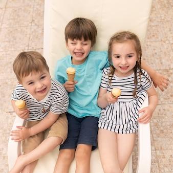 Kinder, die eis essen, während sie auf sonnenliege sitzen