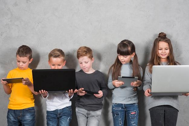 Kinder, die elektronische geräte verwenden