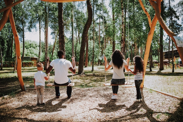 Kinder, die eltern am schwingen-sommer sunny day schwingen