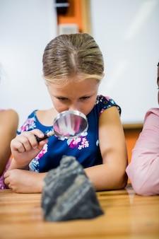 Kinder, die fossilien mit einer lupe schauen