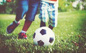 Kinder, die Fußball auf einem Gras spielen