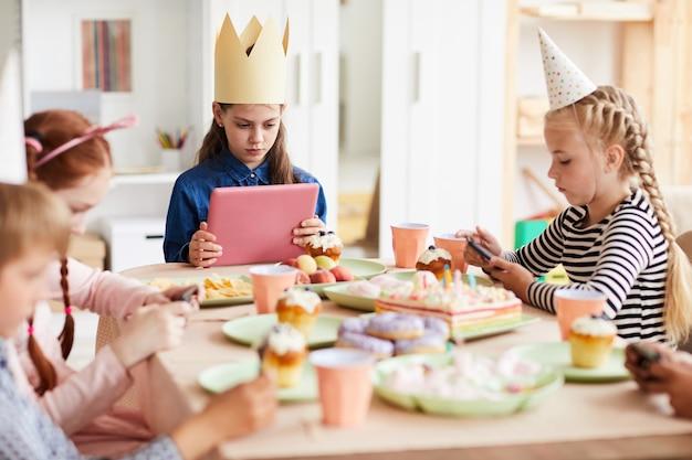 Kinder, die gadgets auf der party benutzen