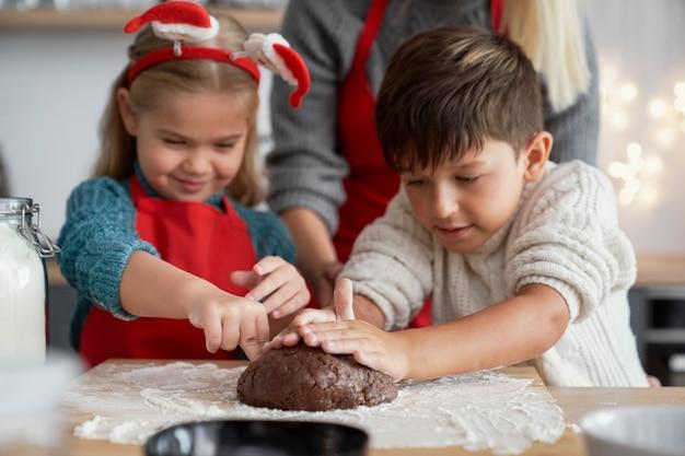 Kinder, die gebäck für lebkuchenplätzchen vorbereiten