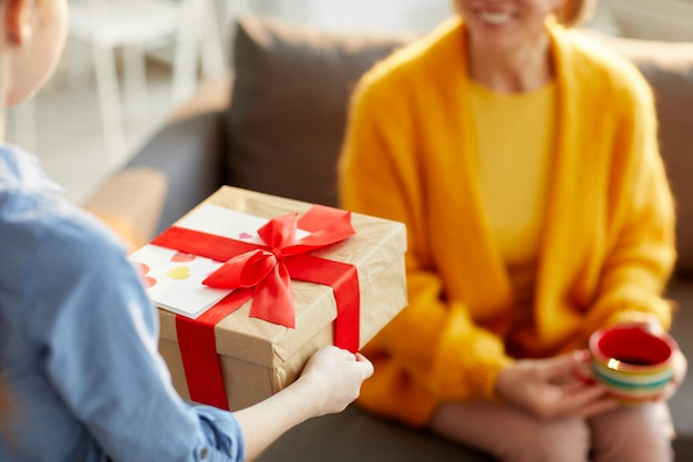 Kinder, die geschenk für mama präsentieren