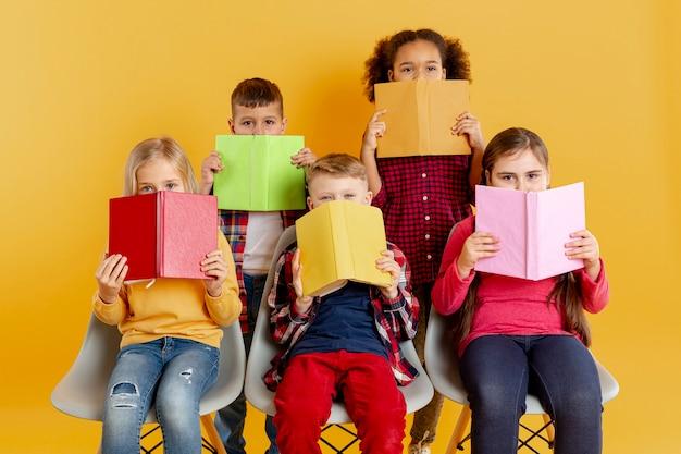 Kinder, die gesichter mit büchern bedecken