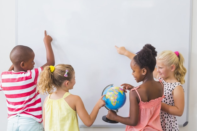 Kinder, die globus im klassenzimmer studieren