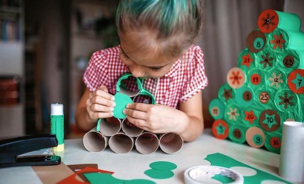 Kinder, die handgemachten weihnachts-adventskalender mit toilettenpapierrollen zu hause machen