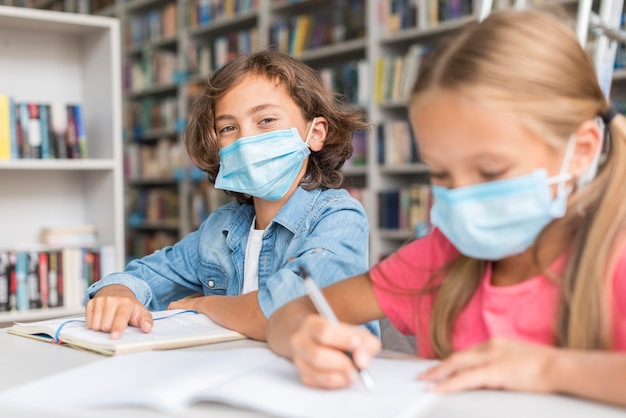 Kinder, die hausaufgaben machen, während sie medizinische masken tragen