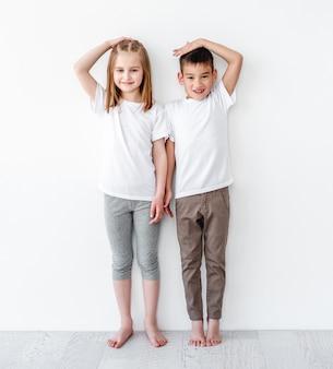 Kinder, die höhe messen und auf weißer wand vergleichen