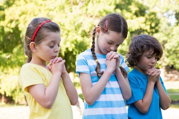 Kinder, die ihre gebete im park sagen