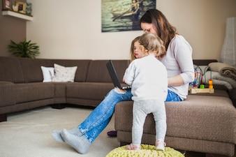 Kinder, die ihre Mutter schaut Laptop betrachten