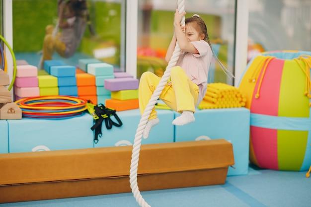 Kinder, die im kindergarten oder in der grundschule übungen zum hochseilklettern in der turnhalle machen. kindersport- und fitnesskonzept.