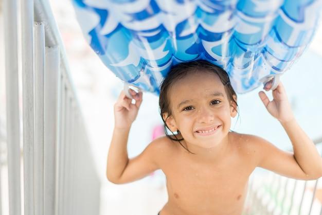 Kinder, die im pool unterwasser genießen, im sommerurlaubsort am pool mit luftmatratze genießend