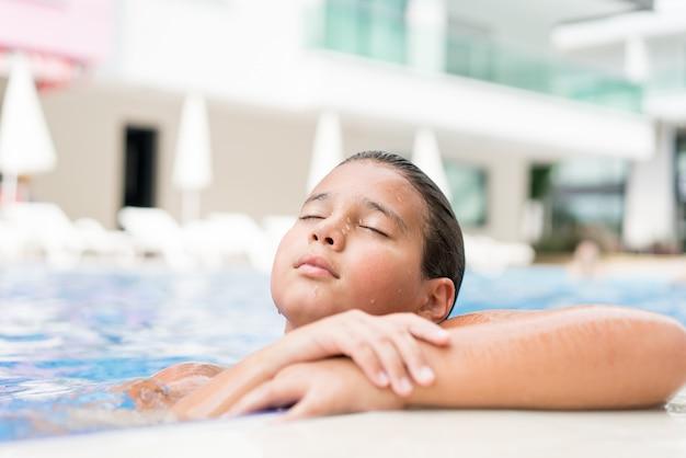 Kinder, die im sommerurlaubsort am pool genießen